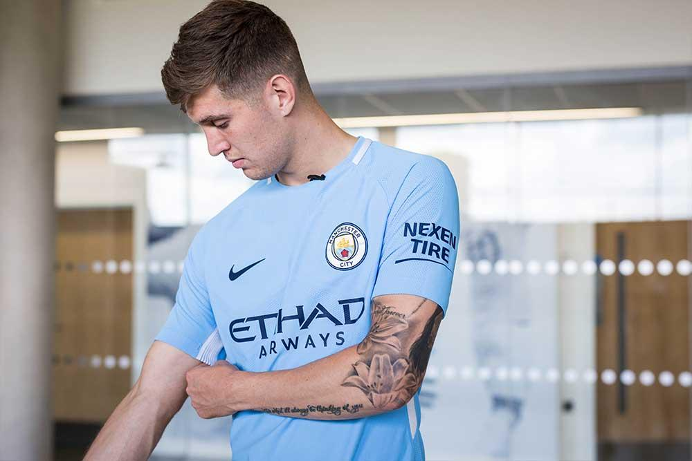 John Stones with the 2017-18 Nike Manchester City home jersey.
