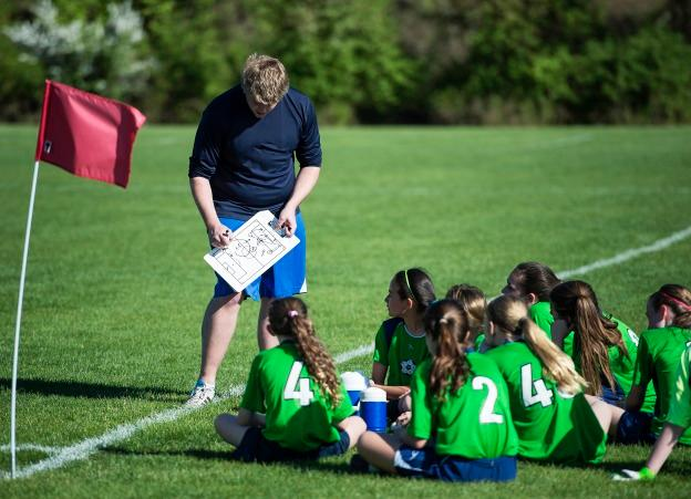 Coach instructs players during halftime of youth girls