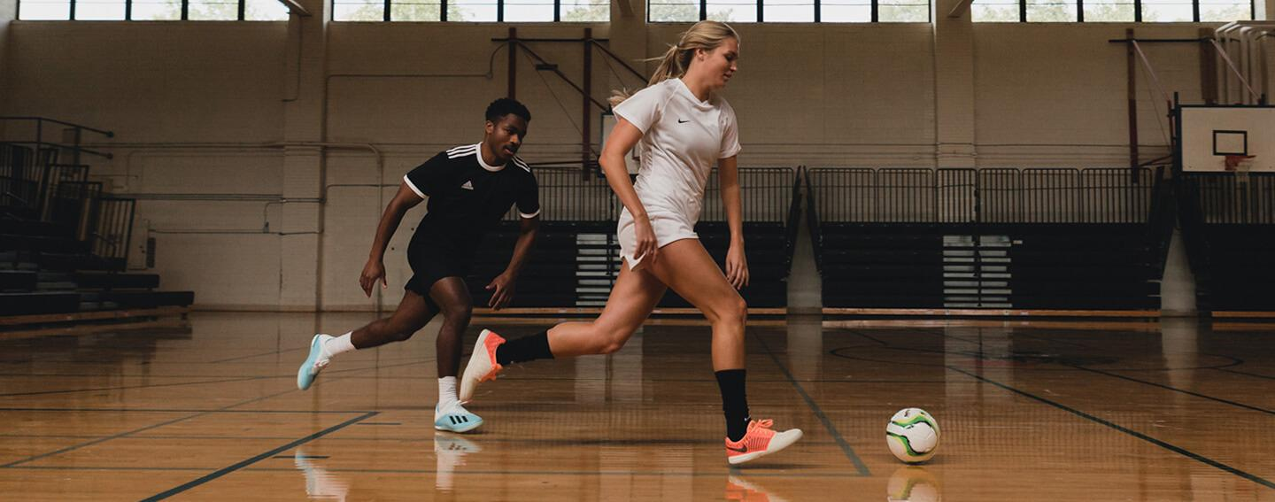 Two indoor soccer players fighting for ball
