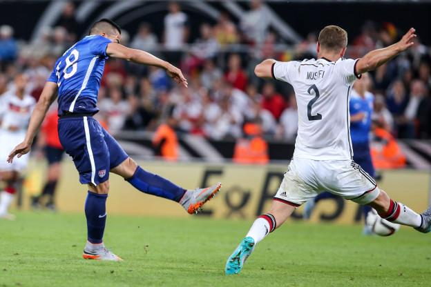 COLOGNE, GERMANY - JUNE 10: Bobby Wood of the USA scores his team's second goal against Shkodran Mustafi of Germany during the International Friendly match between Germany and USA at RheinEnergieStadion on June 10, 2015 in Cologne, Germany. (Photo by Simon Hofmann/Bongarts/Getty Images)